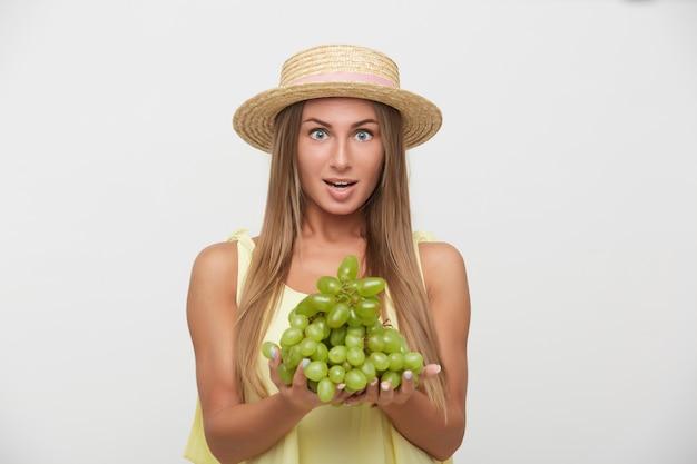 麦わら帽子をかぶった興奮した若い美しい長い髪のブロンドの女性は、目を開けてカメラを見て、白い背景の上に隔離され、上げられた手でブドウを保持しています