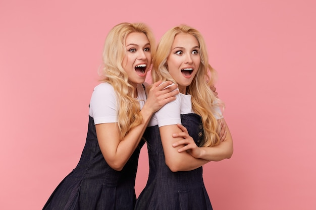 Excited young beautiful long haired blonde women looking surprisedly aside with wide mouths opened while standing over pink background in elegant clothes
