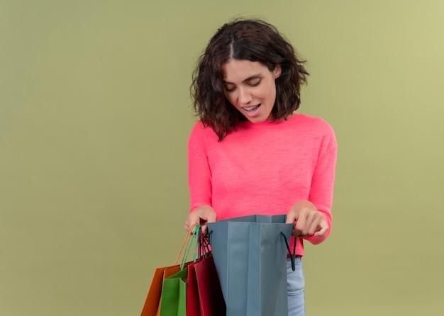 Возбужденная молодая красивая женщина держит картонные пакеты и заглядывает в них на изолированной зеленой стене с копией пространства