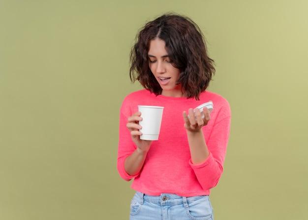 プラスチック製のコーヒーカップを保持しているとコピースペースで孤立した緑の壁でそれを見て興奮している若い美しい女性