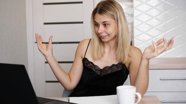 그녀의 노트북 화면을보고 사용하여 제기 팔을 가진 흥분된 젊은 아름다운 여자