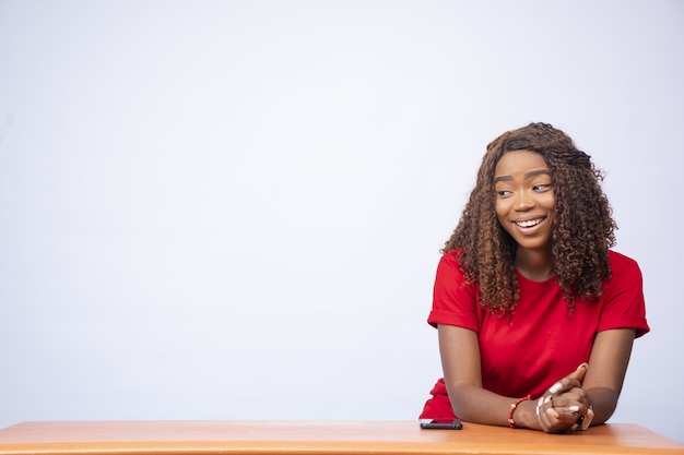 興奮した若い黒人女性は、コンセプトを宣伝しながら、彼女の側のスペースを見つめます。
