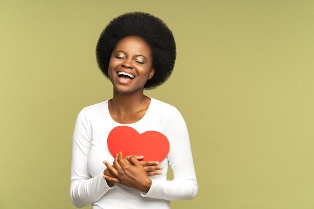 興奮した若い黒人女性がバレンタインデーの休日の幸せな笑顔で赤いハート形のグリーティングカードを保持します。