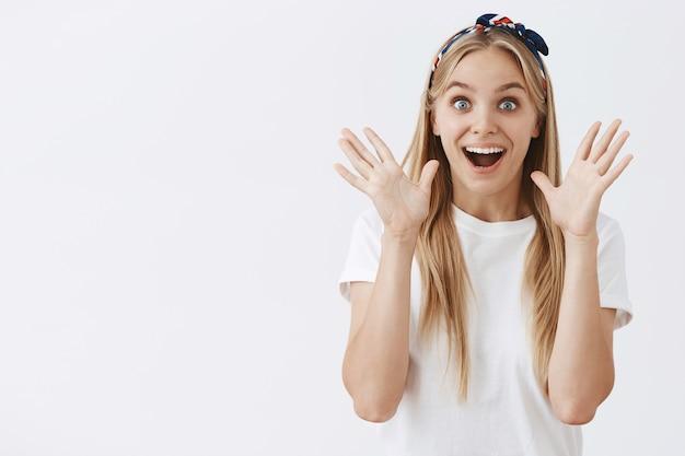 흰 벽에 포즈를 취하는 흥분된 젊은 금발 소녀