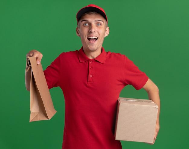 Il giovane ragazzo delle consegne biondo eccitato tiene in mano un pacchetto di carta e una scatola di cartone