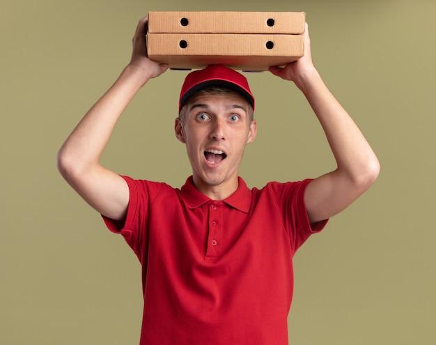 Il giovane ragazzo di consegna biondo emozionante tiene le scatole di pizza sopra la testa isolate sulla parete verde oliva con lo spazio della copia