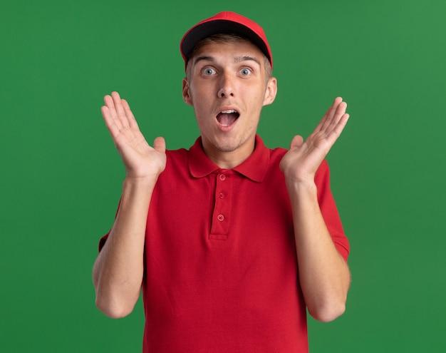 興奮した若い金髪の配達の少年は、コピースペースと緑の壁に分離された上げられた手を持って立っています