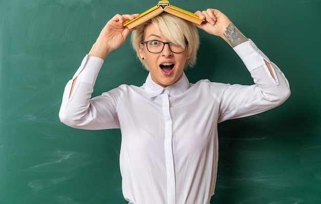 Eccitato giovane insegnante di sesso femminile bionda con gli occhiali in aula in piedi di fronte alla lavagna con un libro sulla testa guardando la telecamera