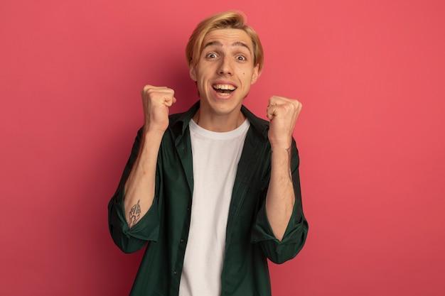 はいジェスチャーを示す緑のtシャツを着て興奮した若いブロンドの男