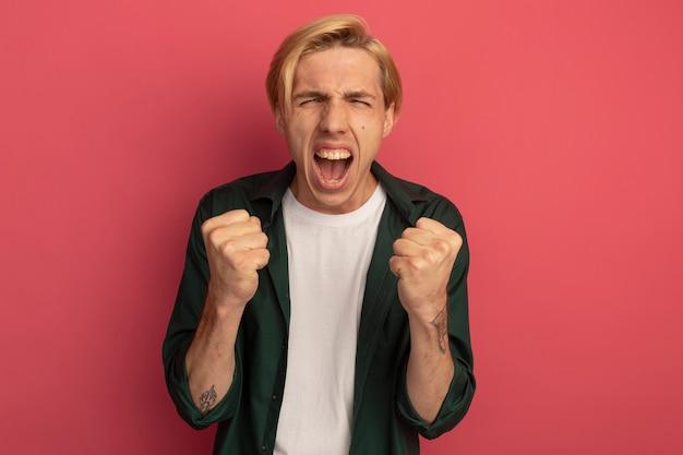 あなたにジェスチャーを示す緑のtシャツを着て興奮している若いブロンドの男