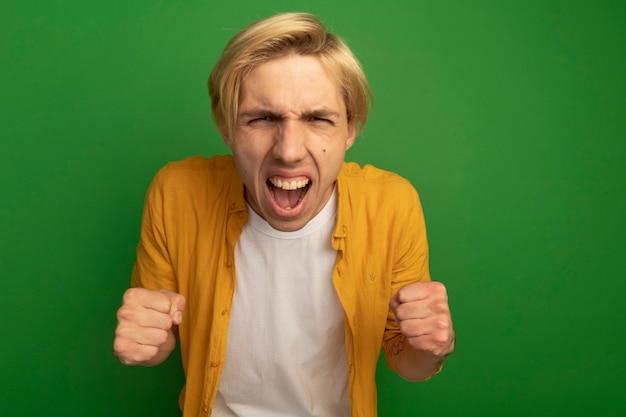 緑に分離されたはいジェスチャーを示す黄色のtシャツを着て興奮した若いブロンドの男