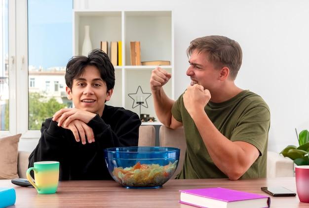 興奮した若いブロンドのハンサムな男がテーブルに座って拳を上げ続け、笑顔の若いブルネットのハンサムな男が手をつないで見ている
