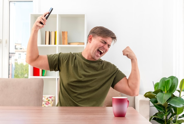 흥분된 젊은 금발의 잘 생긴 남자 컵 시제 팔뚝과 테이블에 앉아 거실 안에 전화를 보유