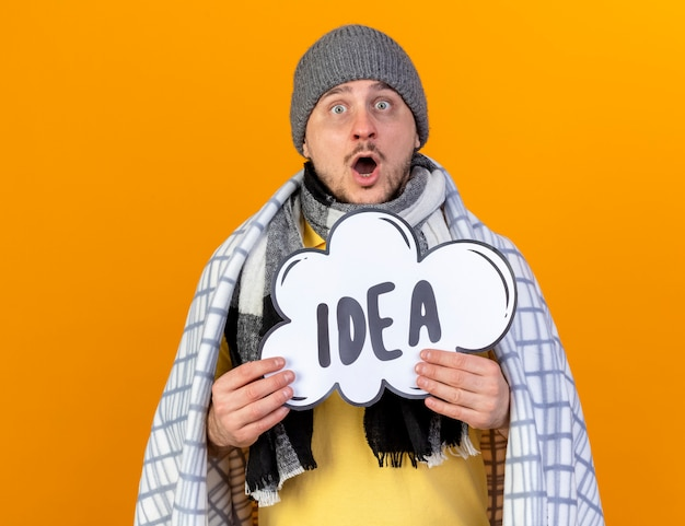 Excited young blonde ill slavic man wearing winter hat and scarf wrapped in plaid holds idea bubble isolated on orange wall with copy space