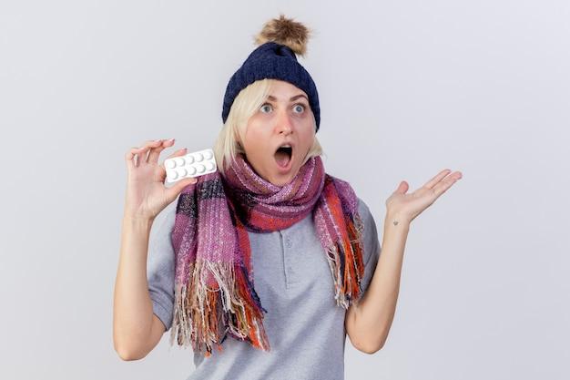 겨울 모자와 스카프를 착용하는 흥분된 젊은 금발의 아픈 슬라브 여자는 제기 손으로 약자와 복사 공간이 흰 벽에 고립 된 의료 약의 팩을 보유