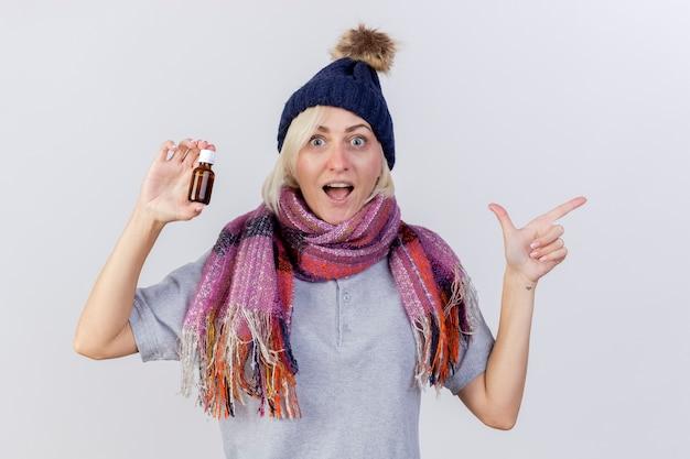 冬の帽子とスカーフを身に着けている興奮した若い金髪の病気のスラブ女性