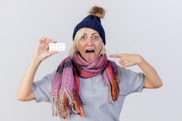 겨울 모자와 스카프를 착용하고 흥분된 젊은 금발의 아픈 슬라브 여자