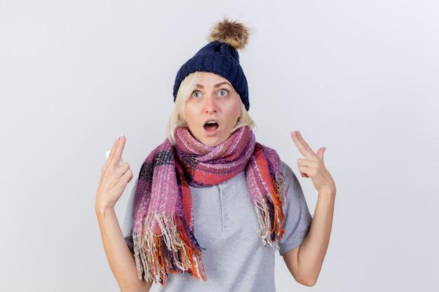 La giovane donna slava malata bionda eccitata che indossa il cappello e la sciarpa di inverno indica con due mani che tengono il pacchetto delle pillole mediche isolate sulla parete bianca con lo spazio della copia