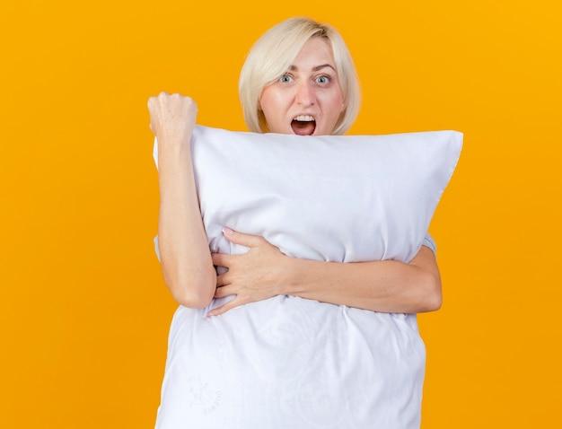 흥분된 젊은 금발의 아픈 여자가 베개를 안고 오렌지 벽에 고립 된 주먹을 유지