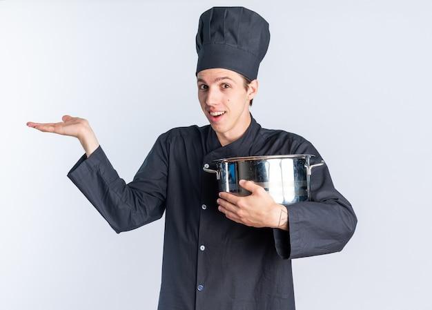シェフの制服と空の手を示す鍋を保持しているキャップで興奮した若いブロンドの男性料理人