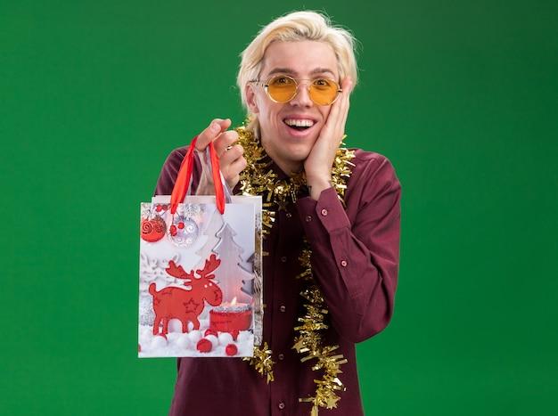 首の周りに見掛け倒しの花輪と眼鏡をかけて興奮した若いブロンドの男は、コピースペースで緑の壁に隔離された顔に手を保つクリスマスギフトバッグを保持しています