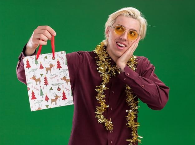 緑の壁で隔離された側を見て顔に手を保ちながらクリスマスギフトバッグを保持している首の周りに見掛け倒しの花輪と眼鏡をかけて興奮した若いブロンドの男