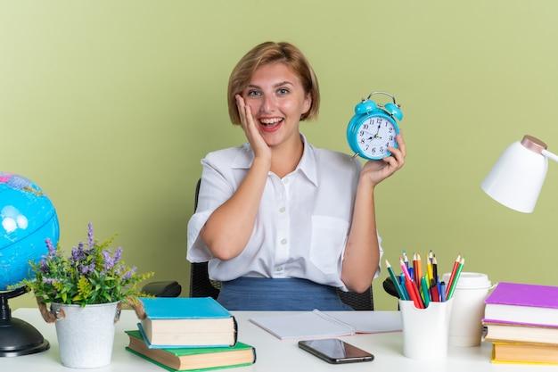 올리브 녹색 벽에 격리된 알람 시계를 들고 얼굴에 손을 대고 카메라를 쳐다보는 학교 도구를 들고 책상에 앉아 있는 흥분한 금발 여학생