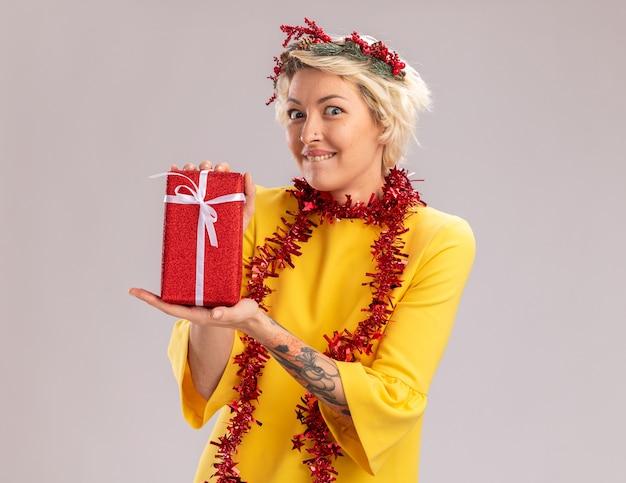 クリスマスの頭の花輪と首の周りに見掛け倒しの花輪を身に着けている興奮した若いブロンドの女性は、白い背景で隔離のカメラを噛む唇を見てクリスマスギフトパッケージを保持しています