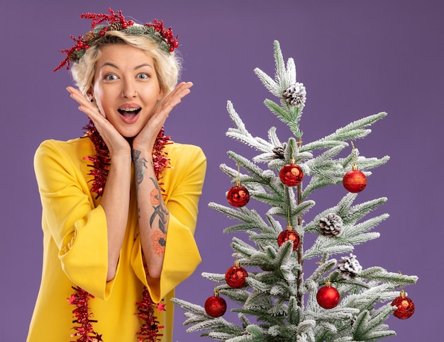 Excited young blonde woman wearing christmas head wreath and tinsel garland around neck standing near decorated christmas tree keeping hands on face looking at camera isolated on purple background