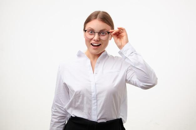 Eccitato giovane donna bionda con acconciatura coda di cavallo alzando la mano ai suoi occhiali e guardando emotivamente la fotocamera con un ampio sorriso, in piedi su sfondo bianco