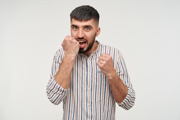 Eccitato giovane maschio bruna dagli occhi marroni con la barba che tiene il pugno alzato vicino al suo viso e che guarda calorosamente, vestito in abbigliamento casual mentre posa sul muro bianco