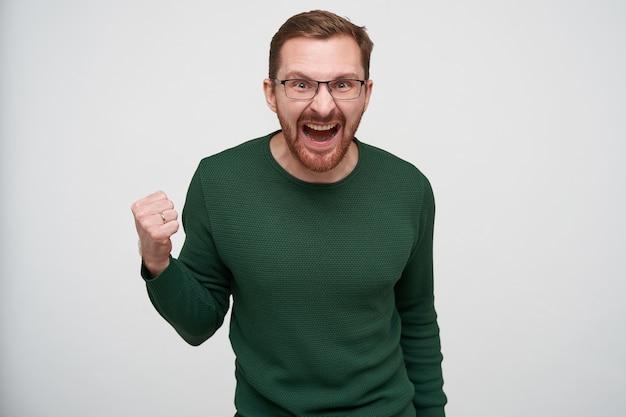 Возбужденный молодой бородатый шатенка в очках хмурится, громко кричит и эмоционально поднимает кулак, одетый в зеленый свитер