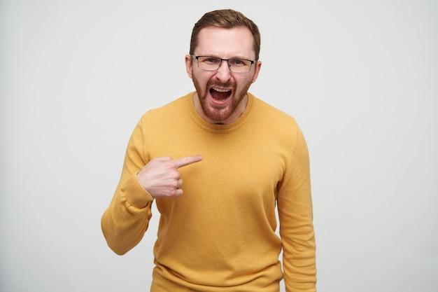 Eccitato giovane maschio dai capelli castani con la barba con un taglio di capelli corto e indossa un pullover casual mentre è in piedi, gridando emotivamente e mostrando su se stesso