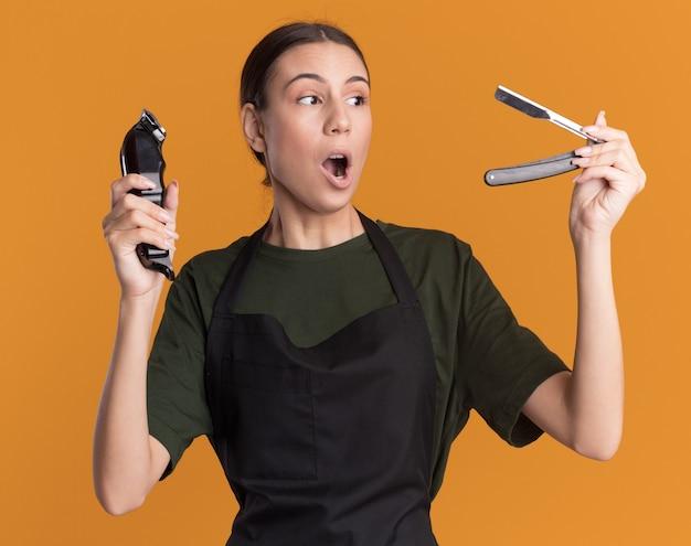 制服を着た興奮した若いブルネットの理髪師の女の子は、バリカンを保持し、ストレートかみそりを見ます