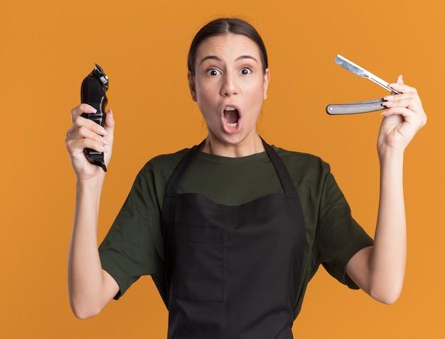 Возбужденная молодая брюнетка-парикмахер в униформе держит машинку для стрижки волос и опасную бритву