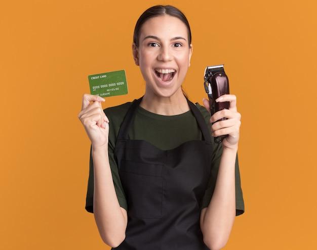 Возбужденная молодая брюнетка-парикмахер в униформе держит машинку для стрижки волос и кредитную карту на оранжевом