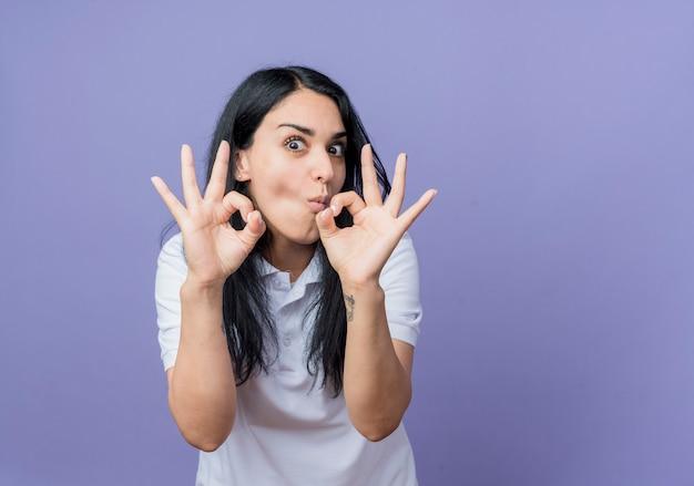 흥분된 젊은 갈색 머리 백인 여자 제스처 보라색 벽에 고립 된 두 손으로 확인 손 기호