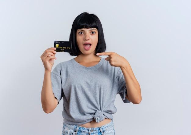 Eccitato giovane ragazza bruna caucasica tiene e punti a carta di credito