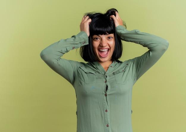 Eccitato giovane ragazza bruna caucasica sollevare i capelli che guarda l'obbiettivo isolato su sfondo verde oliva con spazio di copia