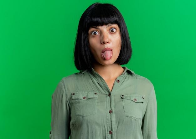 Eccitato giovane ragazza bruna caucasica sporge la lingua guardando la telecamera isolata su sfondo verde con spazio di copia