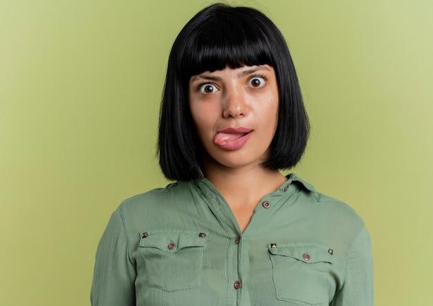 Eccitato giovane ragazza bruna caucasica sporge la lingua guardando la telecamera isolata su sfondo verde oliva con lo spazio della copia