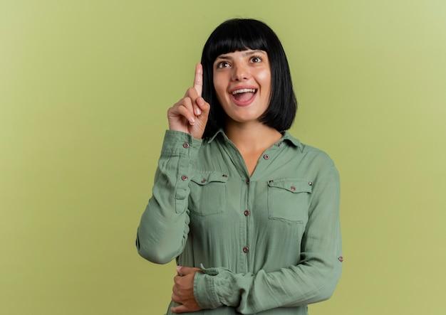 Возбужденная молодая брюнетка кавказская женщина указывает вверх изолированной на оливково-зеленом фоне с копией пространства
