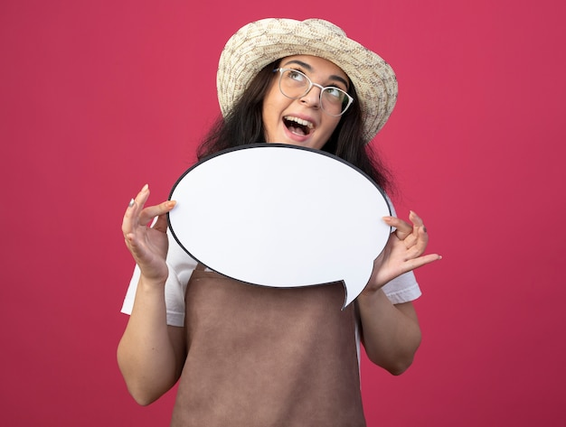 광학 안경 및 원예 모자를 쓰고 제복을 입은 흥분된 젊은 갈색 머리 여성 정원사는 분홍색 벽에 고립 된 찾고 연설 거품을 보유