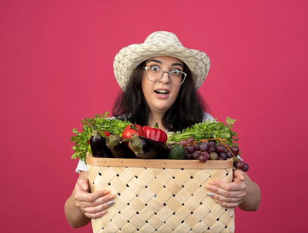 光学メガネと制服を着たガーデニング帽子をかぶった興奮した若いブルネットの女性の庭師は、ピンクの壁に隔離された野菜のバスケットを保持します