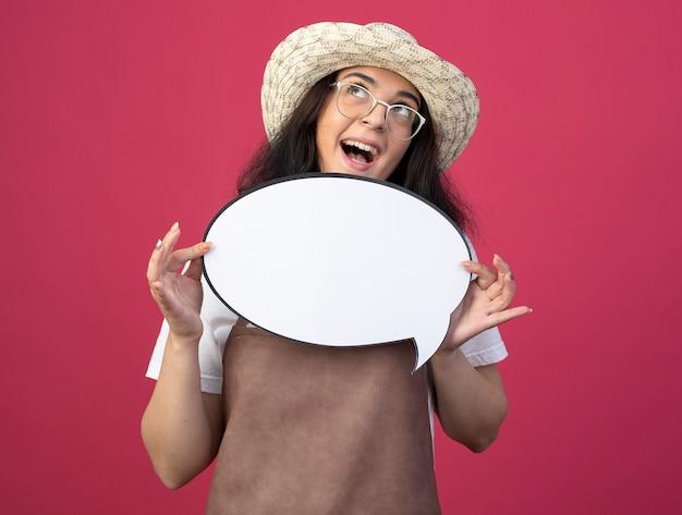 Eccitato giovane giardiniere femminile brunetta in vetri ottici e in uniforme che indossa il cappello da giardinaggio tiene il fumetto che osserva in su isolato sulla parete rosa