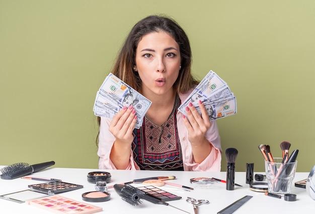 Возбужденная молодая брюнетка девушка сидит за столом с инструментами для макияжа и держит деньги