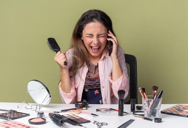 Возбужденная молодая брюнетка сидит за столом с инструментами для макияжа, разговаривает по телефону и держит расческу