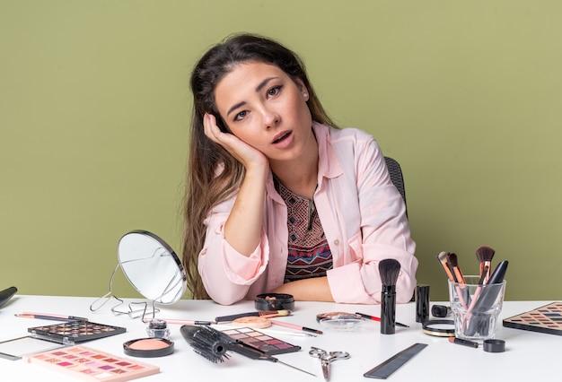 Возбужденная молодая брюнетка девушка сидит за столом с инструментами для макияжа