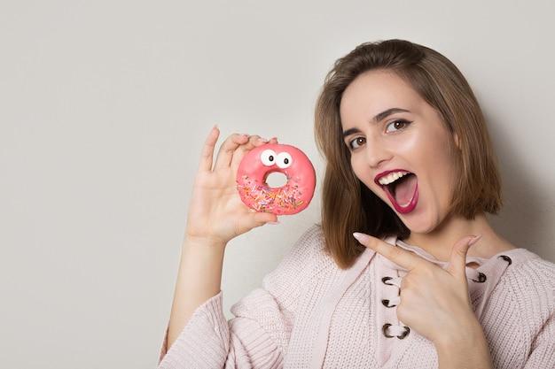 灰色の背景の近くでポーズをとってピンクの釉薬と甘いドーナツを指している興奮した若いブルネットの女性