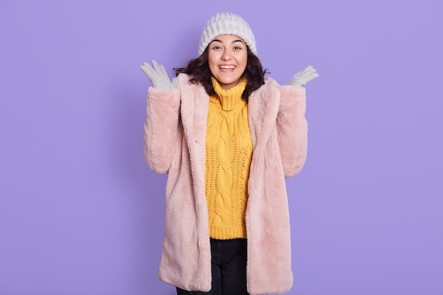 Excited young brunette woman in yellow sweater, fur coat and cap, posing isolated over lilac background, people sincere emotions, girl with toothy smile spreading hands aside.